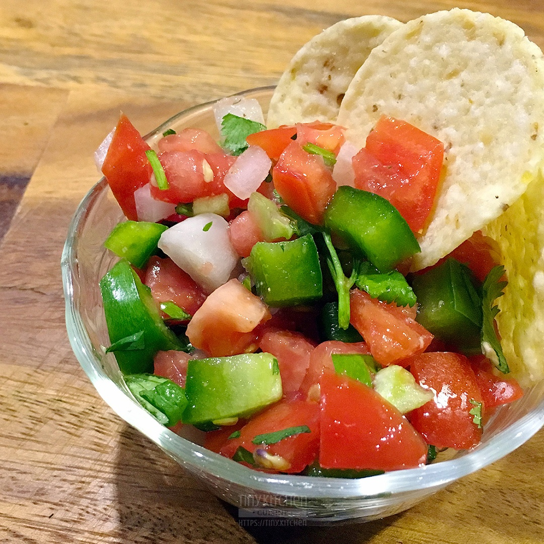 A bowl of pico de gallo with tomato, green peppers, jalapeño, and cilantro topped with two tortilla chips sitting on a wooden cutting board.