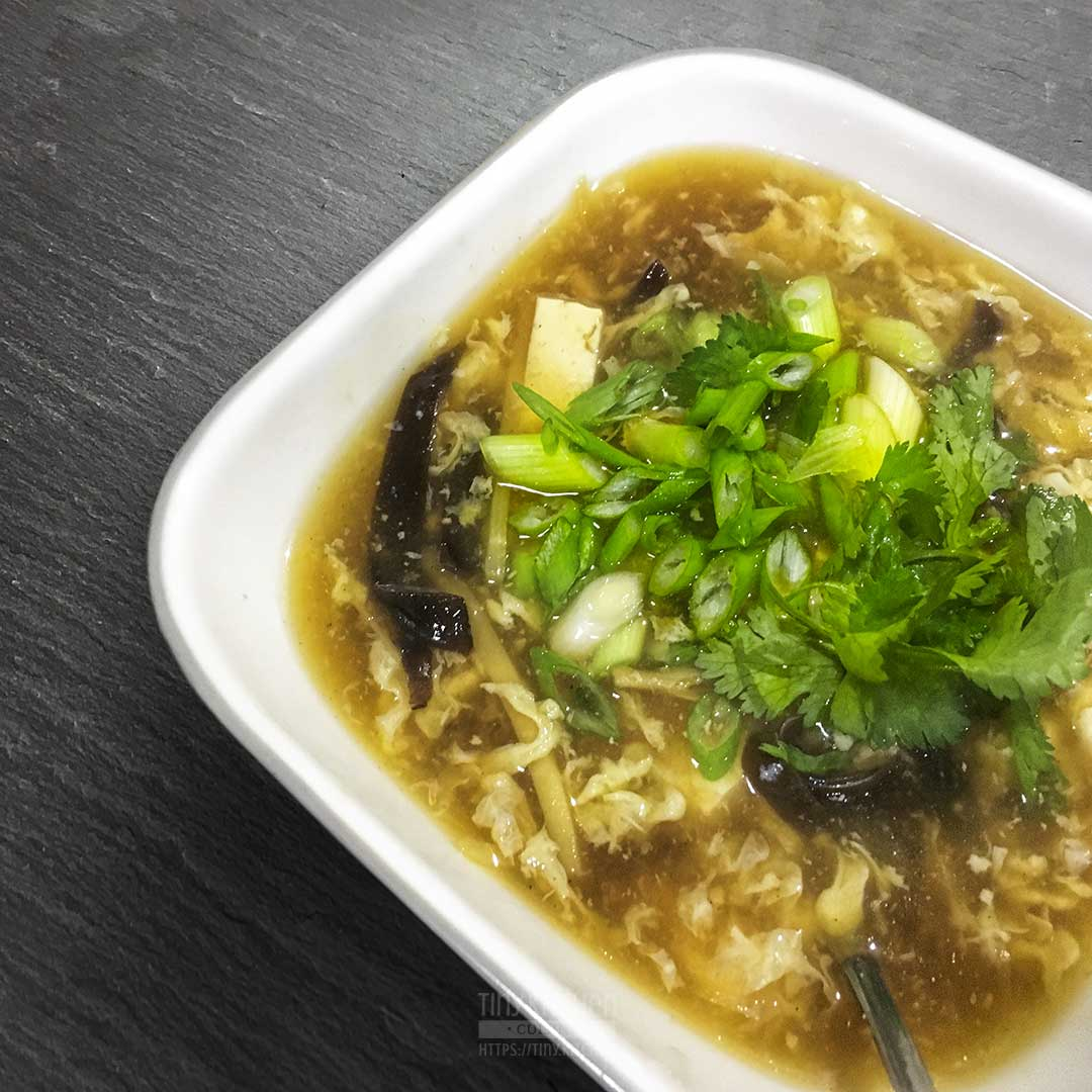 A close up of a bowl of hot and sour soup topped with green onions and cilantro.