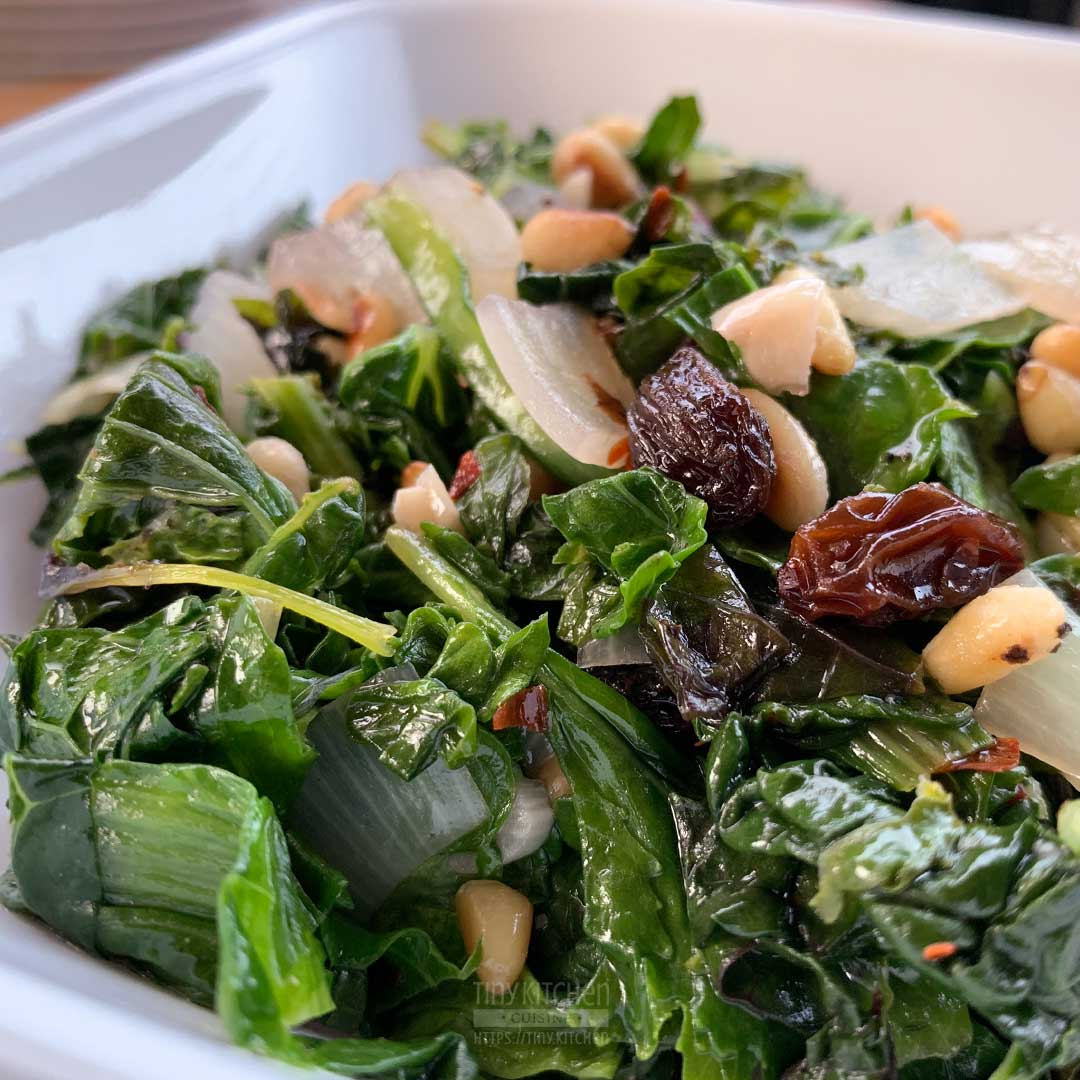 Closeup of a bowl of mixed braised greens topped with toasted pine nuts and raisins.