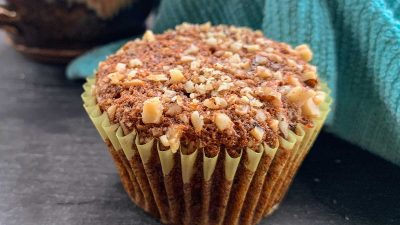 Close up of a banana nut muffin topped with walnuts and a blue cloth lined basket of muffins in the background.